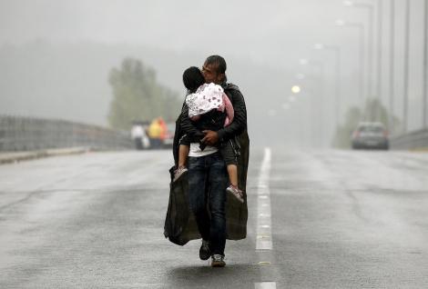 Ένας Σύρος πρόσφυγας φιλά την κόρη του εν μέσω καταιγίδας περπατώντας προς την Ελλάδα στα σύνορα με την ΠΓΔΜ, τον Σεπτέμβριο.